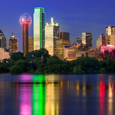 Illuminated by a blend of ambient and artificial light, sunset shimmers off the Dallas skyline as the city is reflected back in the flooded Trinity River. As the sun dips below the horizon, Bank of America Plaza (centered) glows iconic neon green, while lights on the iconic Reunion Tower (center left) flash red and blue, bringing the city to life as the night quickly approaches. (Photo/Stephen A. Masker).